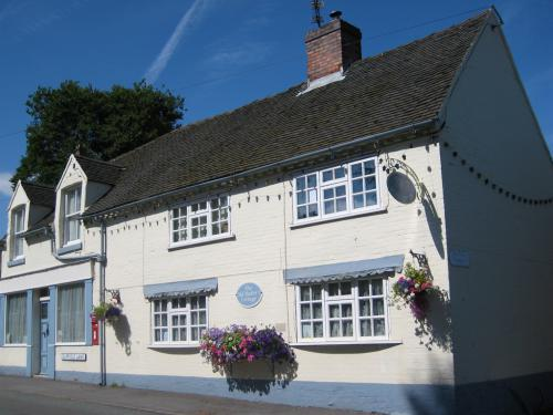 The exterior of The Old Bakers Cottage, set in the heart of Newborough village opposite the Church