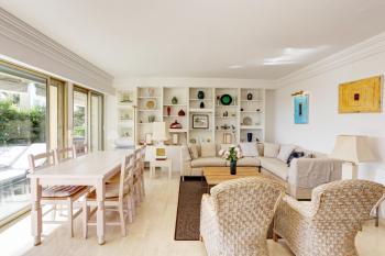 Salon lumineux et confortable avec canapé d'angle et table de repas pour 6 personnes
