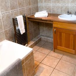 Room Threes bathroom has a large bath with overhead shower, the sink has a side board & cupboard for all your bits and bobs