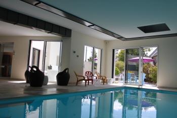Piscine intérieure avec accès direct sur la terrasse