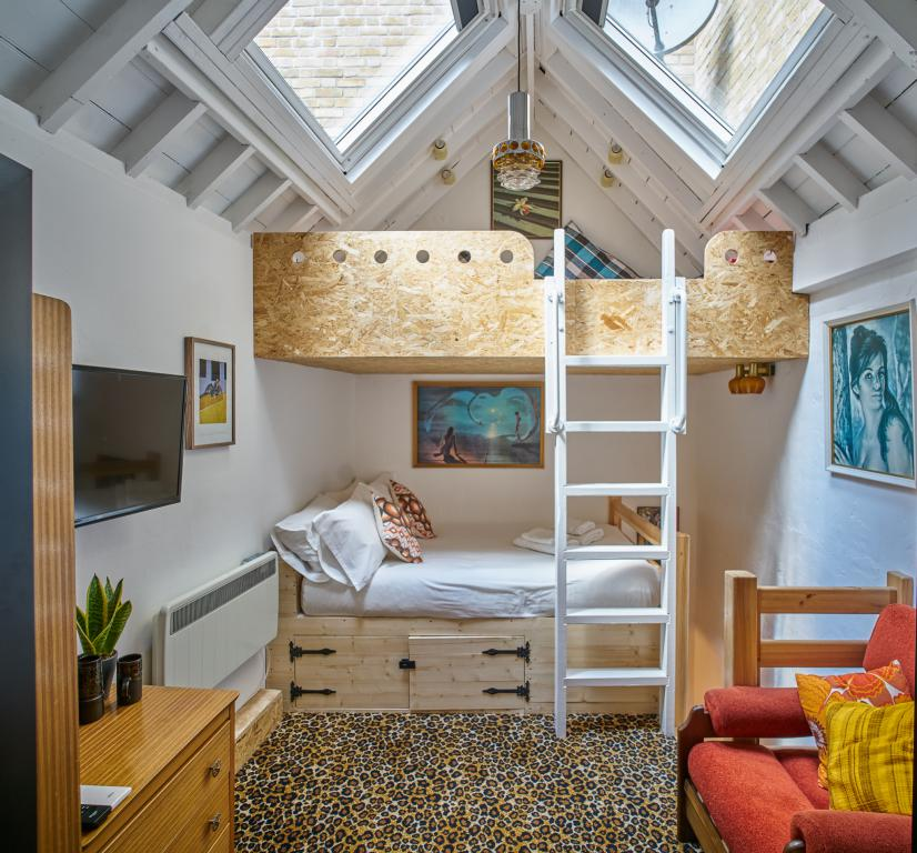view of small double bed and chill out mezzanine above
