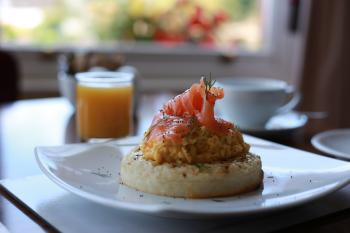 Smoked salmon on scrambled egg and crumpet with poppy seeds and dill.