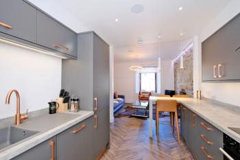 Living area, well-equipped kitchen with breakfast bar, fridge-freezer, dishwasher & induction hob
