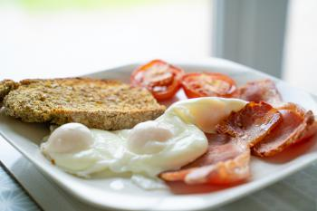 Breakfast - Poached eggs & bacon garnished with toasted wheaten & grilled tomato