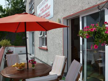 Outside balcony area, overlooking harbour with seated area at Seawinds B&B
