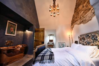 'Speel' with exposed stonework up to 5m, bespoke antique bed and copper bath.