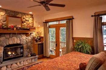 """Oak"" Guest room has a king-size bed, sitting area, fireplace, Jacuzzi, steam shower, and  lake view porch"