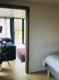 Boshuis zicht op leefruimte vanuit slaapkamer