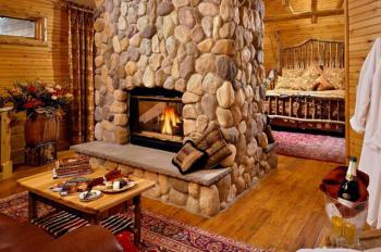 """Birch"" Guest room has a king-size bed, sitting area separated with a double-sided fireplace, Jacuzzi, and lake view porch"