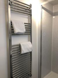 Deluxe King bedroom newly refurbished Ensuite with large chrome towel rail to keep the room warm.