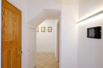 Spacious Hallway with Walk-in cupboard housing dining and outdoor chairs, washing machine and supplies.  Secondary cupboard gives some storage as well as housing supplies including high chair