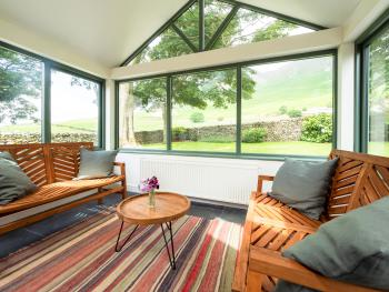 Large conservatory room offering sweeping view of Black Comb fell