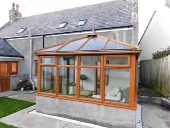 Conservatory with infrared heating when needed, cosy sofa and doors to join the garden