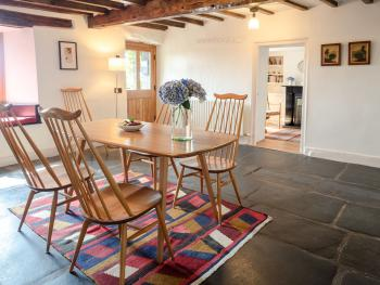 Wayside Cottage - Characterful dining room with exposed beams and original slate floor, completed with a wood burner stove