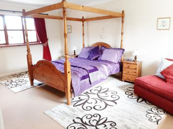 Bedroom with four poster bed and futon