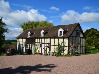 Haywain (pink door), Sparrows Nest (green door) and Willow Cottage (Blue door)