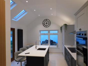 Stylish kitchen with social seated island and smart TV wall mounted