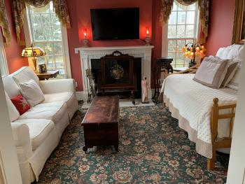 Parlor of suite has trundle bed, sofa, flat screen and fireplace