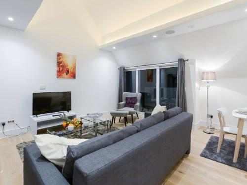 Relaxing seating  area which consist of TV a three seater sofa bed
