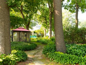 Steps away from guest rooms outdoor netted dining in backyard gardens under giant Bur Oaks.