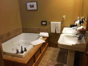 Oak bathroom with double pedestal sinks and jaccuzzi tub