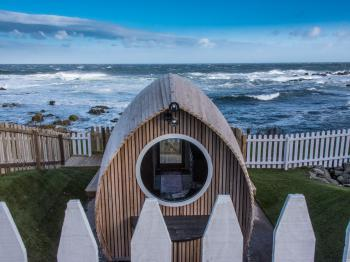 Door to the shore is a luxurious Eco Pod crafted in the style of an upturned boat made from Larch Wood.