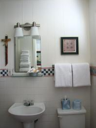 Bathroom of motor lodge room, each have a tub/shower and amenities and hair dryer.