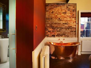 Copper bath in the bedroom space with separate walk-in shower room