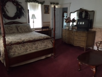 Willow room with a queen four poster bed, private bath with shower, and a loveseat located on the main floor.