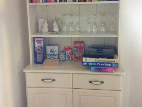 Dresser on the landing with Books, magazines, Board Games & Jigsaws, Wine Glasses, Champagne Flutes for guests use.
