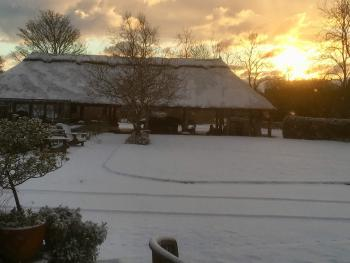 Sunrise over open thatched barn