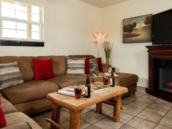 Chestnut chalets living room with huge wrap around couch, 55 inch TV and electric fireplace.