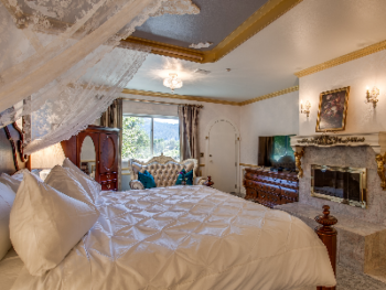 Palace Suite King bed adorned with delicate, lace curtains with center view of wood-burning fireplace.