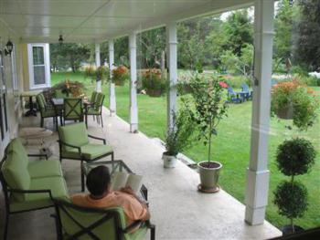 Our covered veranda is a great place to relax overlooking our expansive lawn and gardens.