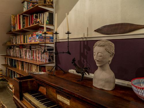 Close up of square piano with board games & DVDs in background