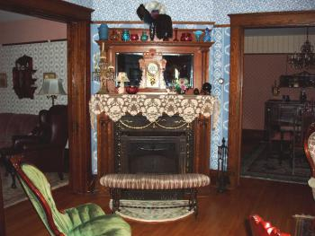 The original brass and iron fireplace situated on an angle between dining room and parlors.
