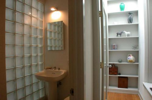 Glass-bricked bathroom wall lets in diffused, ambient light.
