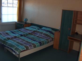 Das größere Schlafzimmer mit Doppelbett und Schreibtisch besitzt neben Plissee-Rollos auch komplette Rollläden