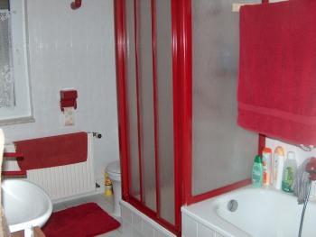 Das größere Badezimmer mit Dusche, WC, Badewanne und Spiegelschrank erstrahlt in Rubinrot