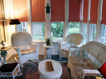 Three season enclosed porch located just off the dining room--an ideal place to read, relax and visit.
