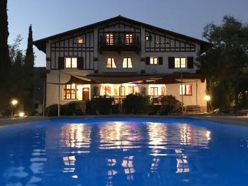Maison principale côté piscine, au crépuscule