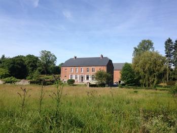 La maison coté jardin et terrasse vue de la prairie de l'autre coté du ruisseau qui traverse la propriété