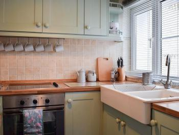 Fully equipped kitchen with cooker, hob, kettle, toaster and microwave and an array of cutlery, crockery, pots and pans.