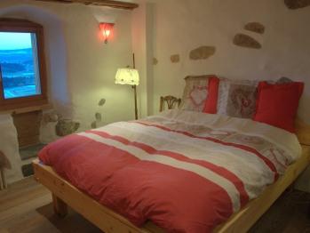 Au Soleil de Gruyères chambre double, lit artisanal bois massif, sol chêne, poutres 14ème siècle
