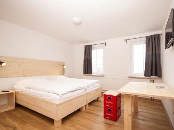 Die Doppelzimmer verfügen über ein großes gemütliches Bett, einen Schreibtisch mit Sitzgelegenheit und einen Flachbild-TV