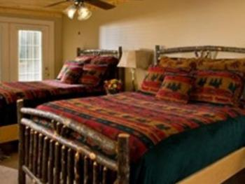 """A """"Deluxe King"""" with a queen size bed and a double bed and back porch overlooking the back yard."""