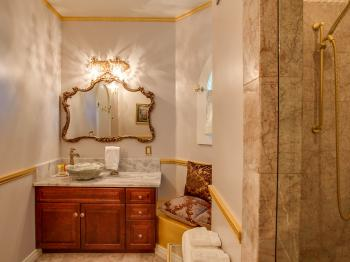 Palace Suite bathroom offering marble shower with dual shower heads and stone sink with marble counter.