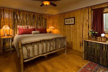 """""""Forest"""" Guest room has a king-size bed, sitting area, fireplace, Jacuzzi, and  lake view patio"""