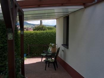 Die überdachte Terrasse im Garten dient auch als Raucherinsel
