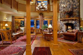 The Great Room with its cathedral ceiling and huge stone fireplace with screened in porch just beyond is a beautiful gathering area for guests.